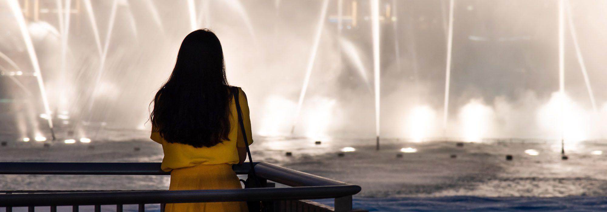 Frau vor der Dubai Fountain am Burj Khalifa